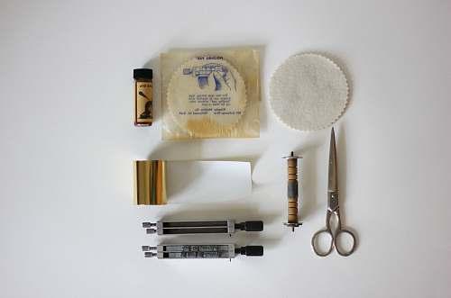 tool silver scissors beside brown rod flatlay
