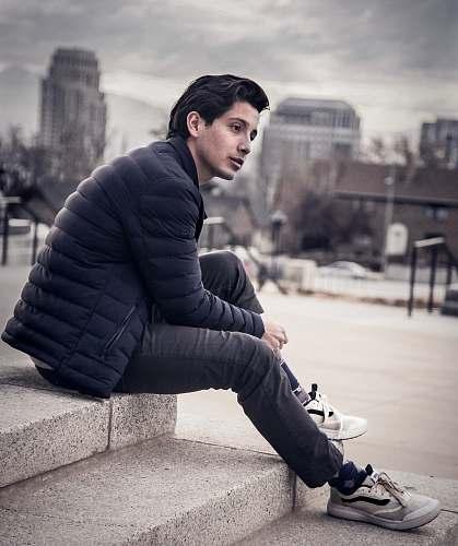footwear man sitting on concrete surface apparel