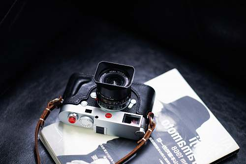 camera black and gray digital camera on book electronics