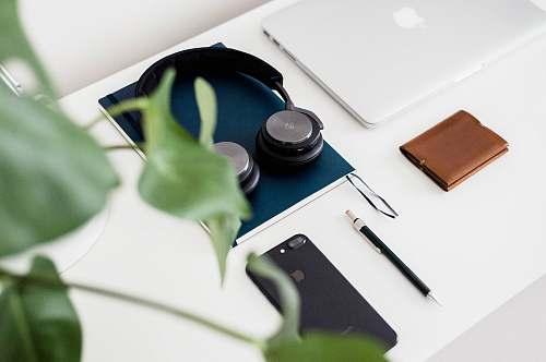 tabletop black and gray headphones on blue book desktop