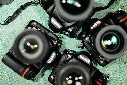 camera four black Nikon DSLR cameras on green textile nikon