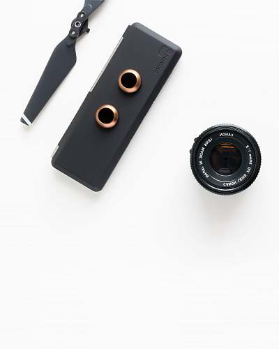 modern closeup photo of black camera attachments on white surface minimal
