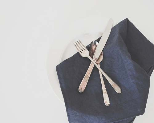 linen gray fork, spoon, and butter knife on plate with black table napkin table