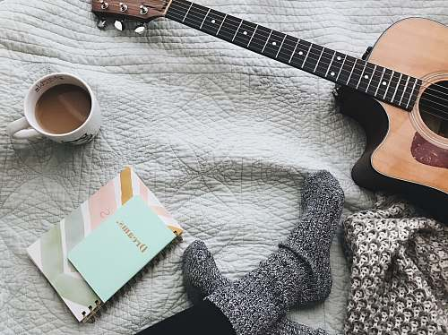 guitar person wearing gray socks near acoustic guitar music