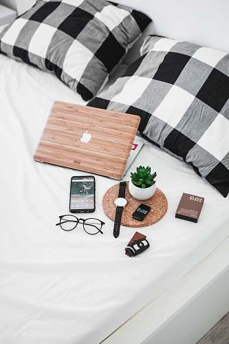 blanket smartphone, eyeglasses, watch, and vehicle fob on bed timișoara