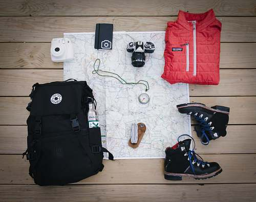 person black hiking backpack near white Fujifilm instax mini camera near black leather boots, red half-zip jacket, gray pocket watch on white map people
