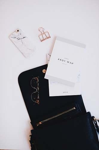 desk gold framed sunglasses, black phone case near gold clip grey