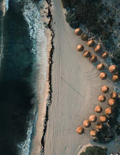landscape aerial photography of brown cottages on seashore at daytime drone view
