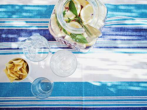 tablecloth lime juice bottle beside shot glasses on table glass