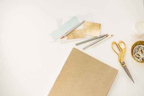 gold yellow handled scissors beside brown paper desk