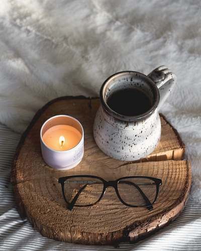 cup black-framed eyeglasses beside candle coffee cup