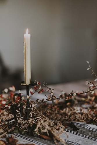 photo fire lighted candle on candlestick on top of table grey free for commercial use images