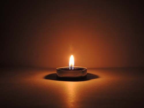 fire round ceramic bowl with lighted candle brown