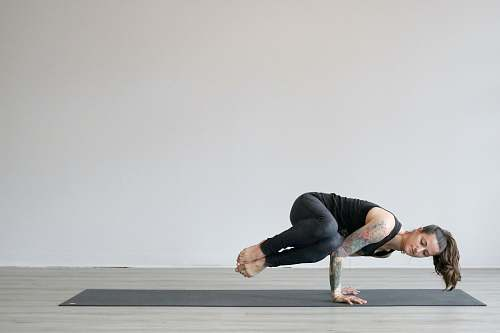 human woman in black tank top and gray leggings doing yoga exercise