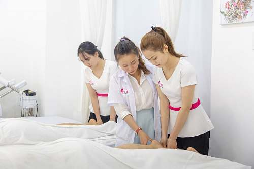 person one woman assisting another woman in massaging massage