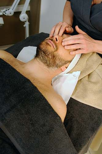person sleeping man while having massage face