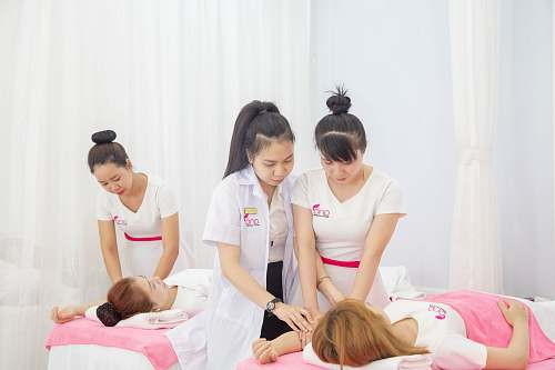 person three women standing beside bed massage