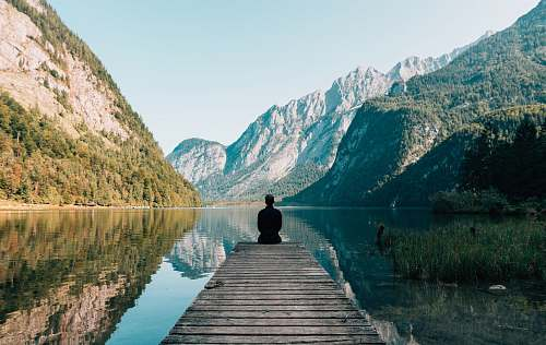 travel man sitting on gray dock meditation