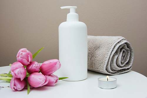 beauty white plastic pump bottle beside pink tulips and gray towel flora