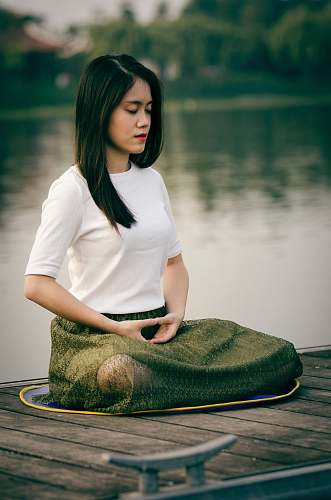 people woman meditating on wooden dock during daytime female