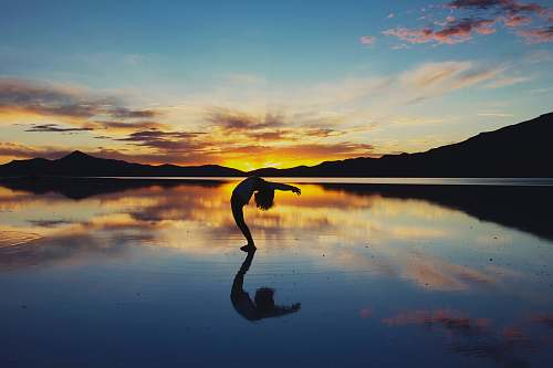 mountain silhouette photography of woman doing yoga ocean