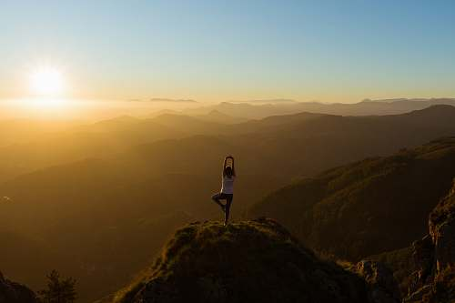 nature woman stretching on mountain top during sunrise sunset