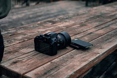 black DSLR camera on top of brown wooden table