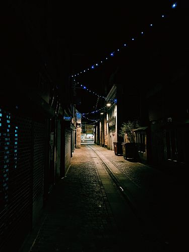 empty alley between houses and stores at night