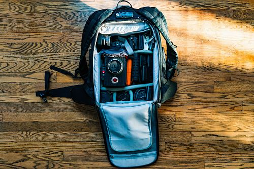 flat-lay photography of DSLR camera in backpack on wood parquet floor