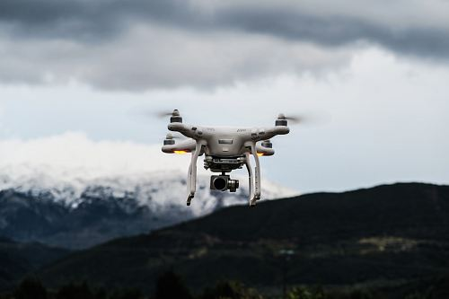 photo flying white quadcopter drone at daytime free for commercial use images