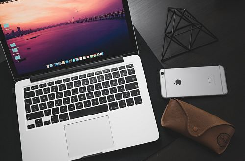 photo MacBook Pro beside space iPhone 6 on black wooden surface free for commercial use images