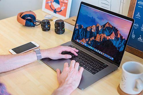 photo MacBook Pro turned on beside white ceramic mug free for commercial use images