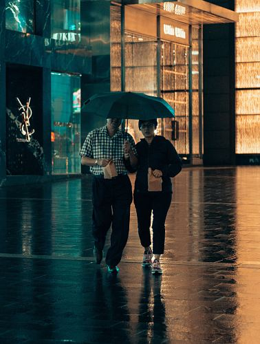 photo man and woman under same umbrella walking while holding paper bags free for commercial use images