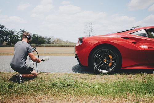 man behind car holding microphone measuring sound