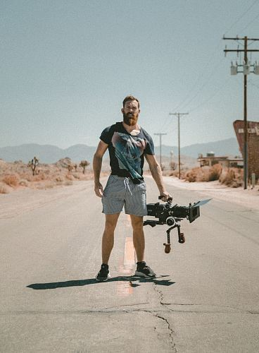 man holding camera standing on road during daytime