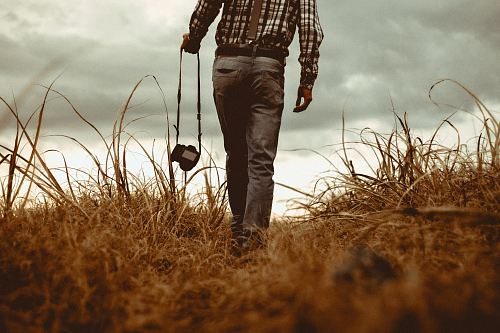 man holding DSLR camera walking through brown grass