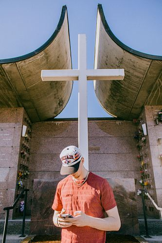 photo man holding smartphone and standing near cross statue free for commercial use images