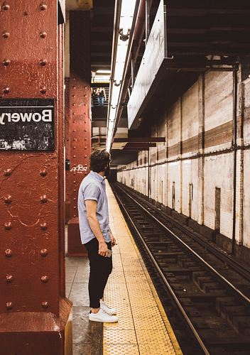 photo man standing beside subway platform free for commercial use images