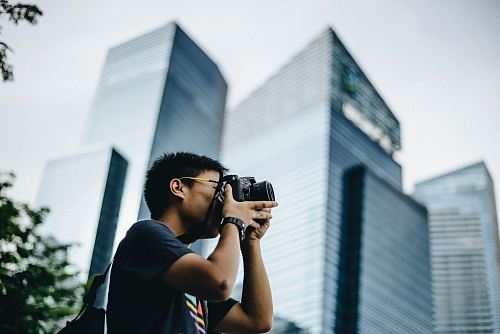 man wearing black t-shirt holding DSLR camera