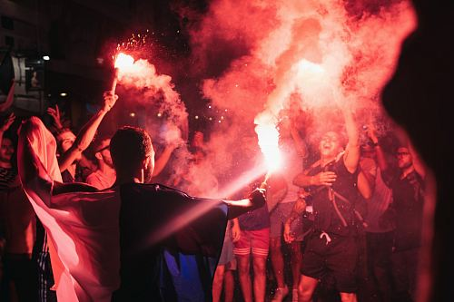 people holding firecrackers at night