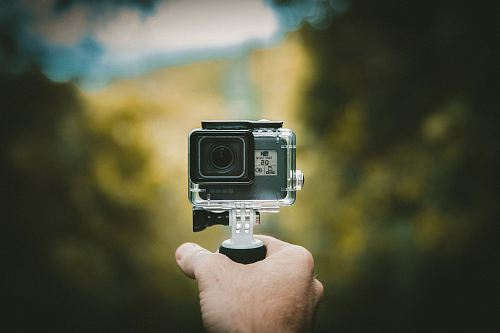 photo person holding action camera free for commercial use images