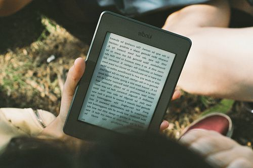 photo person holding black Amazon Kindle e-book reader free for commercial use images