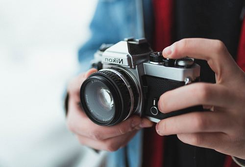 photo person holding black and gray Nikon DSLR camera free for commercial use images