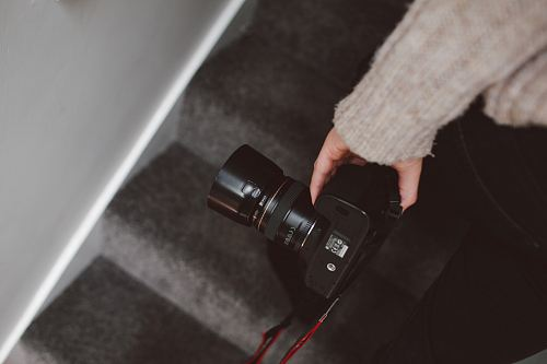 person holding black DSLR camera close-up photo