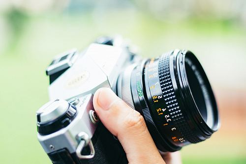 photo person holding black DSLR camera free for commercial use images
