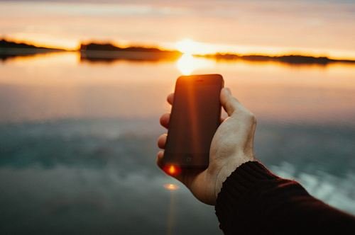 person holding black iPhone near lake during sunset
