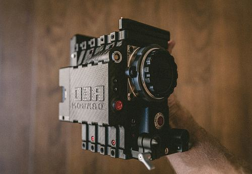 person holding black Red Dragon land camera