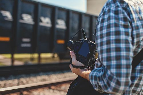 photo person holding DSLR camera near cargo container during daytime free for commercial use images