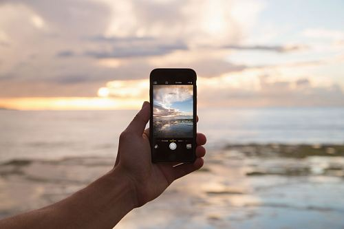 photo person holding smartphone showing ocean free for commercial use images