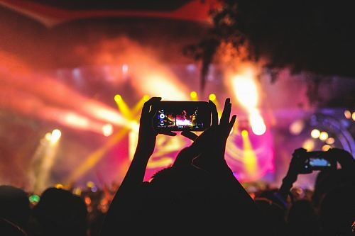 photo person holding smartphone taking video of a concert near stage with lights during nighttime free for commercial use images